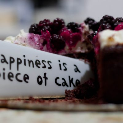 a piece of birthday cake saying happiness is a piece of cake